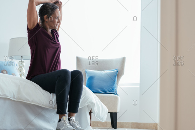 Fit mature woman stretching arms while sitting on bed at  home