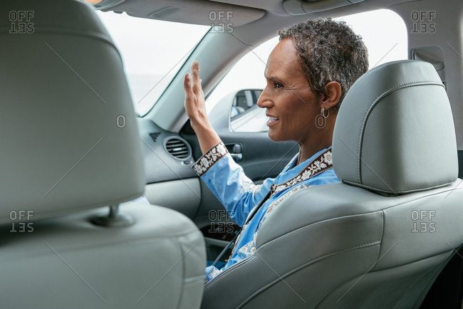 Side view of mature woman gesturing while sitting on front seat of car