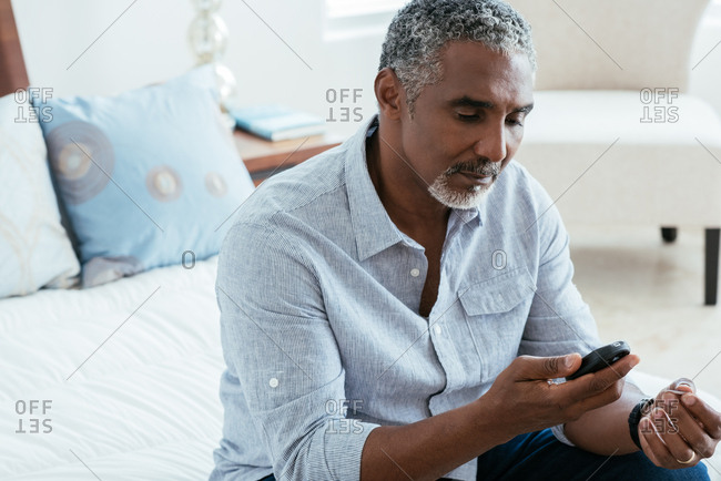 Mature man examining blood sugar level on glucometer while sitting on bed at home