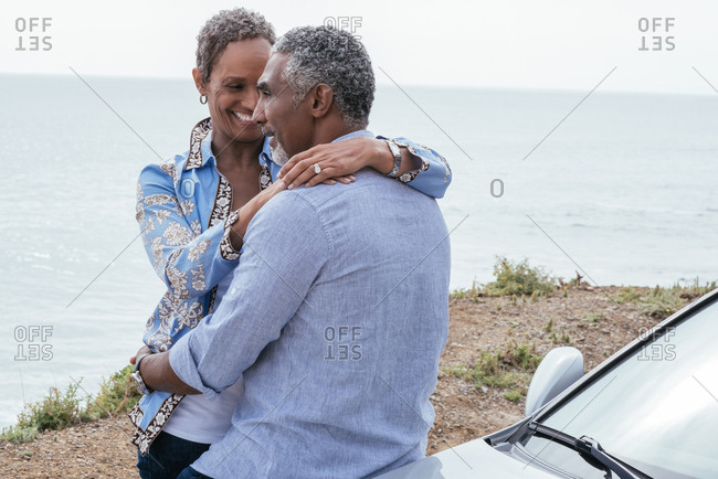 Happy mature woman embracing man leaning on Car against sea