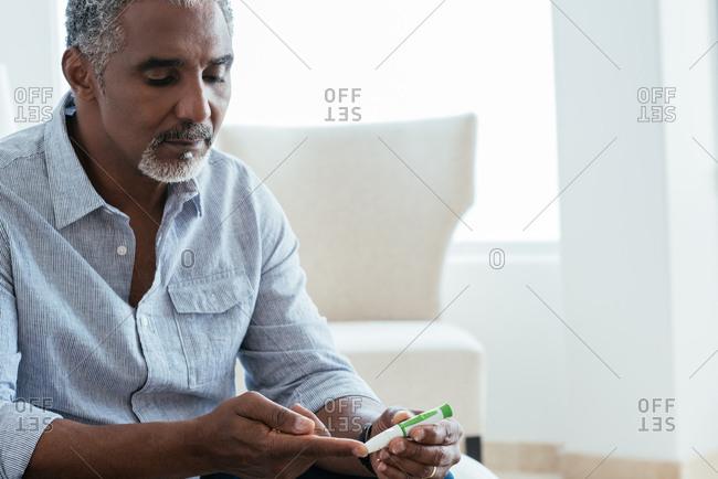 Mature man testing blood sugar level at home