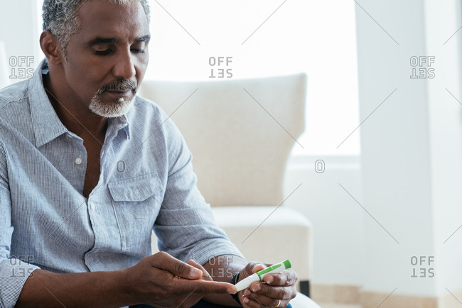 Mature man testing blood sugar level at home