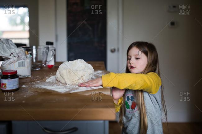 Girl by raw dough ball