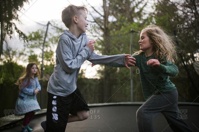 Kids wrestling around on trampoline