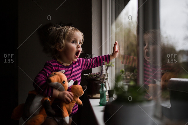 Shocked toddler at window with dolls