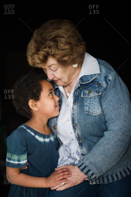 Interracial grandmother and granddaughter hugging