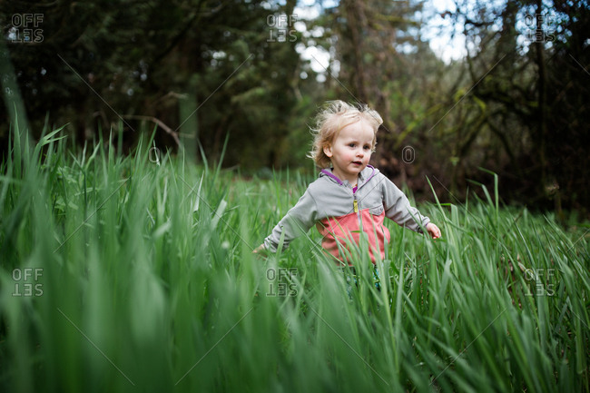 Toddler girl running through tall grass