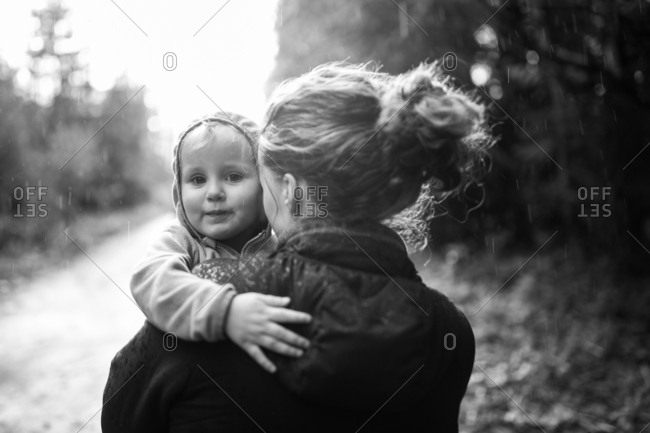 Mom carrying girl walking in forest