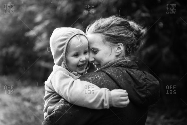 Mom hugging girl walking in forest