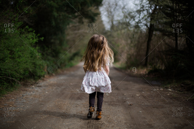 Girl walking away down rural path