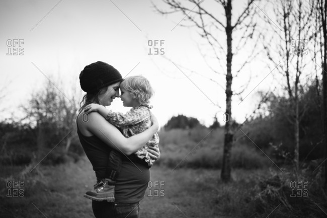 Mom holding toddler girl in a clearing