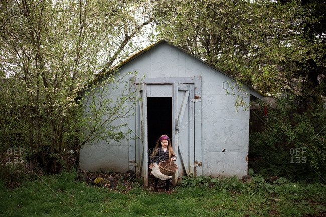 Girl with basket leaving shed