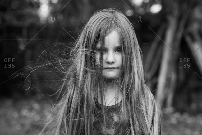 Girl with hair covering face in yard