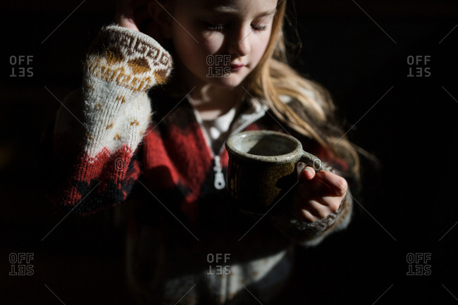 Girl in shadows holding a mug