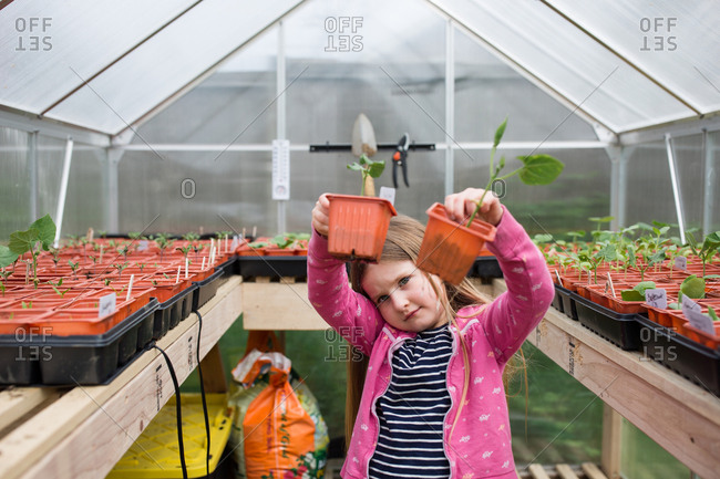 Girl holding pots with new plants