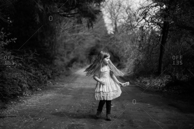 Girl twirling on rural dirt road