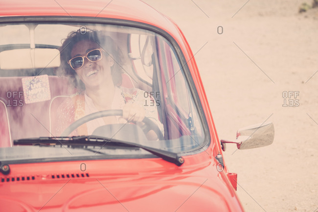 Woman laughing in vintage car on beach