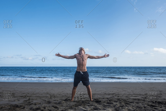 Man standing carefree on a beach