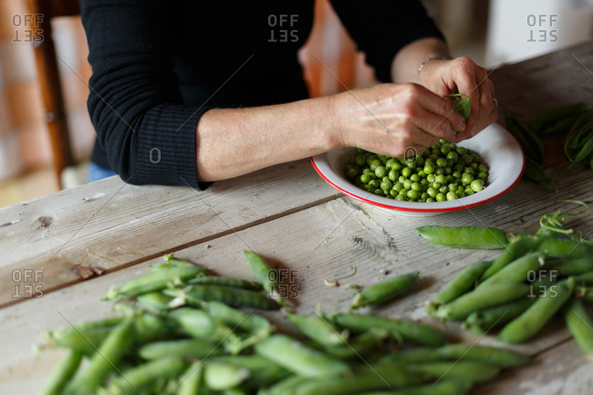 Hands opening up fresh peas