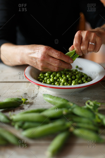 Hands opening fresh peas