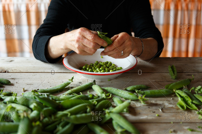 Person at table opening fresh peapods