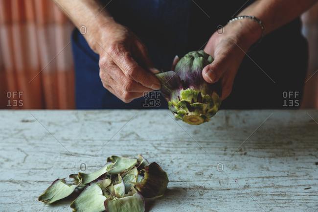 Person preparing fresh artichokes