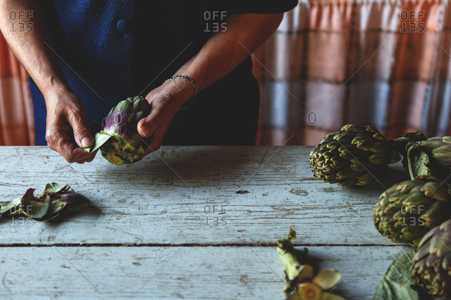 Person peeling fresh artichokes