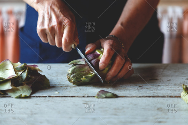Person cutting fresh artichokes