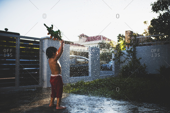 Boy splashing with toy in yard