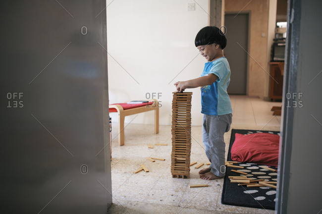Boy playing on tower built from blocks