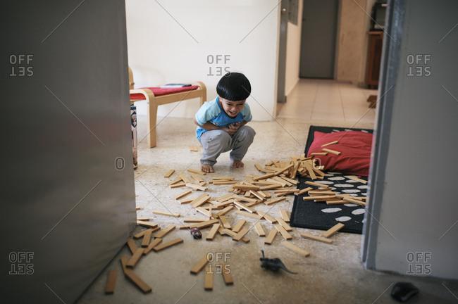 Boy laughing at spilled block toys