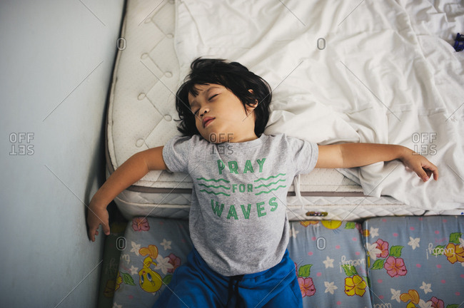 Boy fast asleep on mattresses