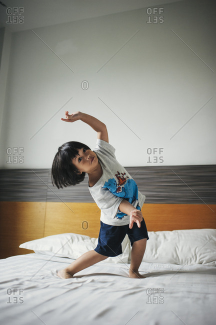 Boy dancing around on bed