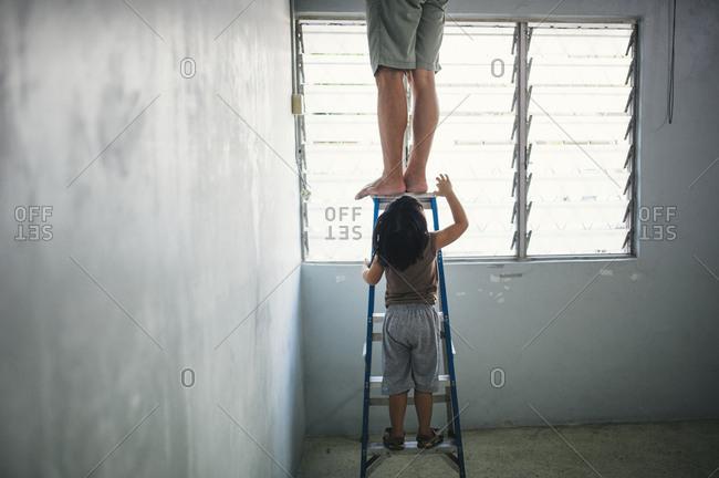 Boy climbing ladder under man
