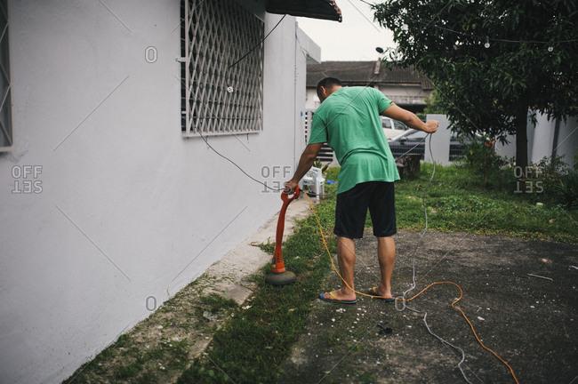 Man in Malaysia trimming lawn