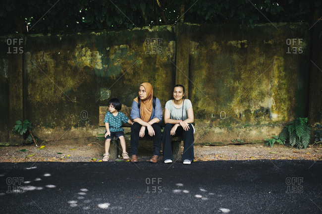 Boy and two women waiting on bench
