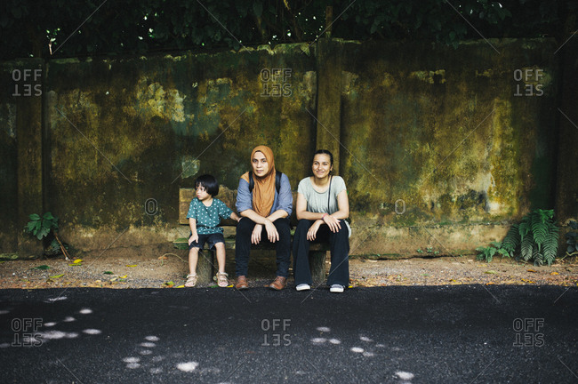 Boy and two women waiting on a bench