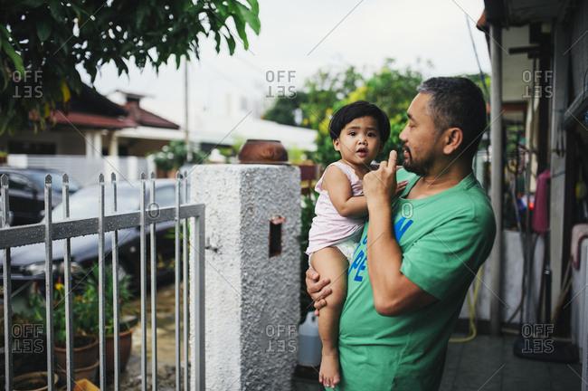 Dad holding toddler in yard, Malaysia