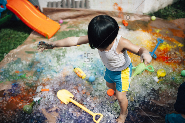 Boy playing with paint and ice
