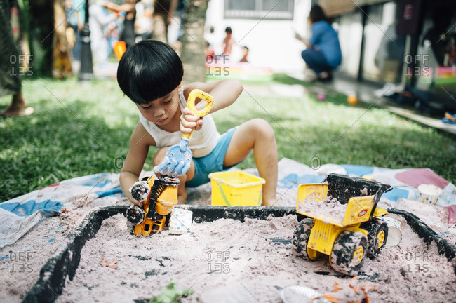 Boy playing with toys in small sandbox
