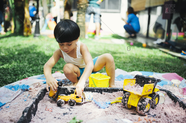Boy playing with toys in a small sandbox