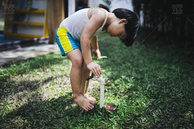Boy rinsing off feet at tap in yard