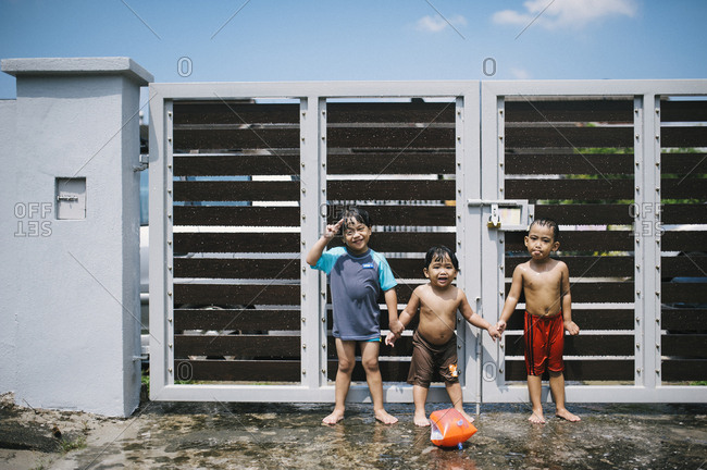 Three wet kids in yard, Malaysia