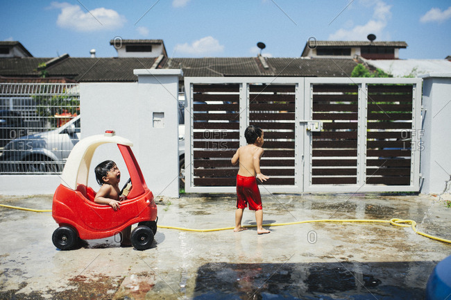 Crying toddler with boy playing in yard