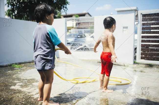 Boys playing with hose in yard