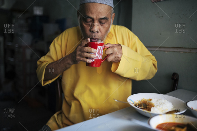 Older Malaysian man cooling his drink