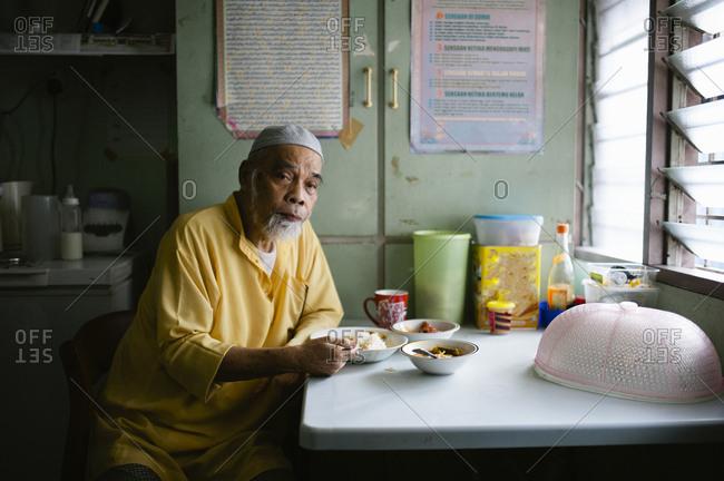 Malaysian man eating at a table
