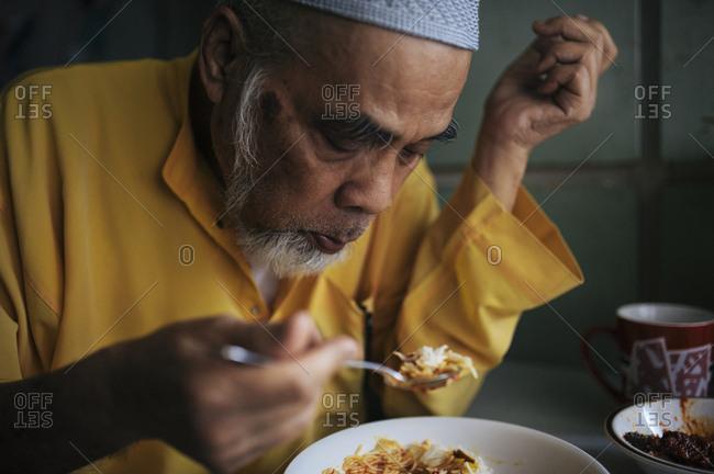 Malaysian man eating rice dish at table