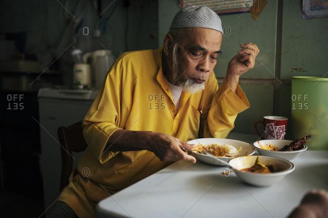 Malaysian man eating dish at table