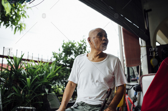 Older Malaysian man sitting outside home